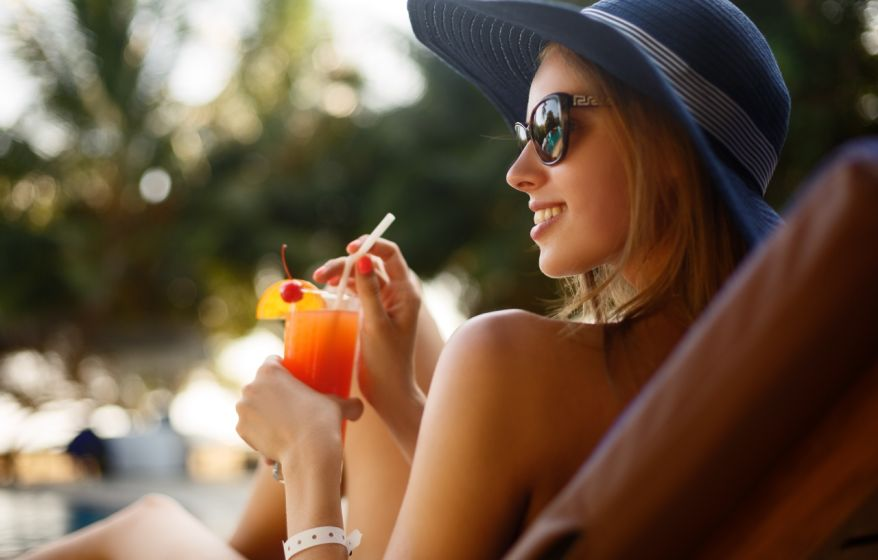 Portrait of young woman with cocktail glass chilling in the tropical sun near swimming pool on a deck chair with palm trees behind. Vacation concept