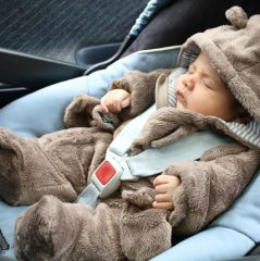 Baby in bear one piece sleeping in a car seat