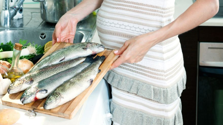 Smiling housewife cooking trout