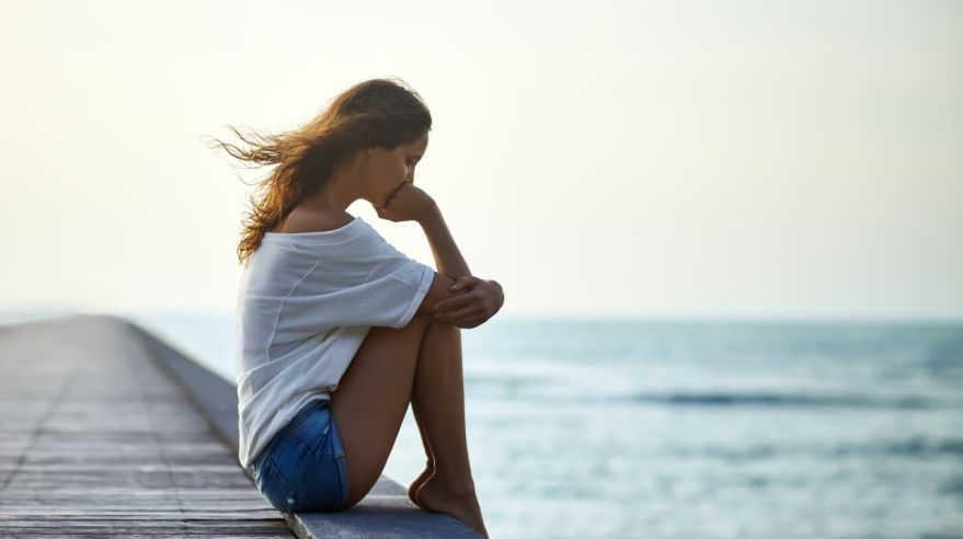 Sad lonely beautiful woman sitting on the pier