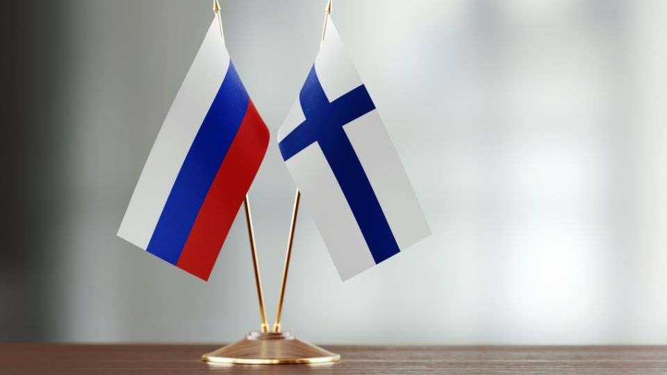 Russian And Finnish Flag Pair On A Desk Over Defocused Background