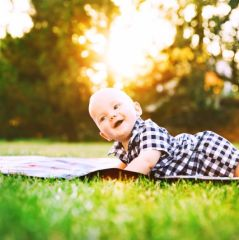 Happy adorable child baby boy lying on the grass and laughing in summer day on nature.