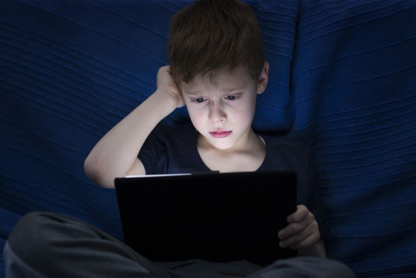 A boy with tablet at night