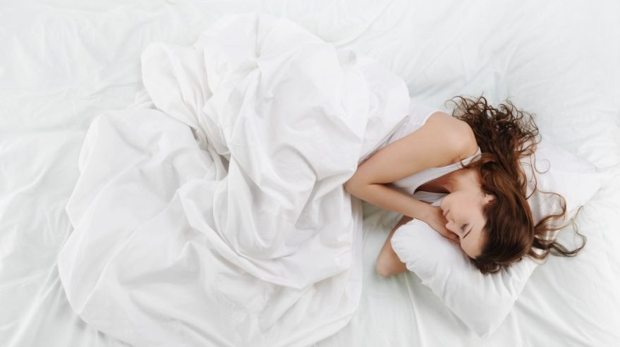 Woman sleeping peacefully in a bed with clean white sheets