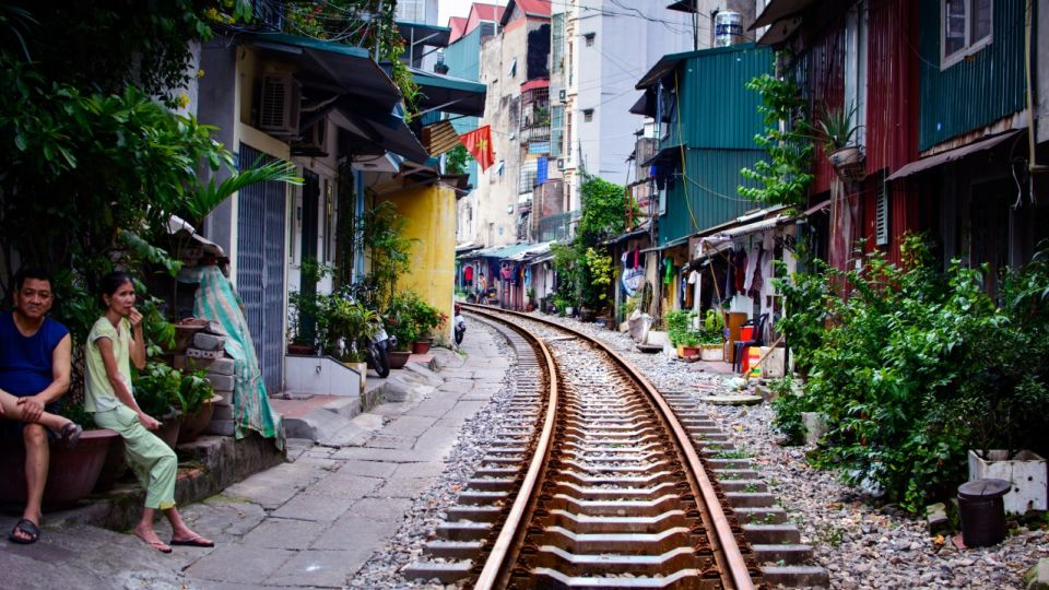 Hanoi train street with railroad and residents sitting
