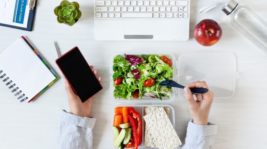 Hands of business woman working on phone and eating healthy business lunch at workplace. Vegetables and fresh green salad in lunch box on working desk with laptop and other office supplies.