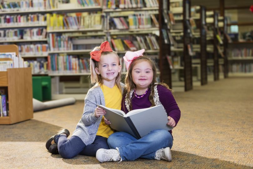Girl with down syndrome and friend reading in library
