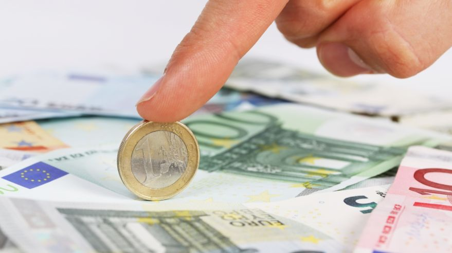 Man's finger holding one euro coin on euro banknotes