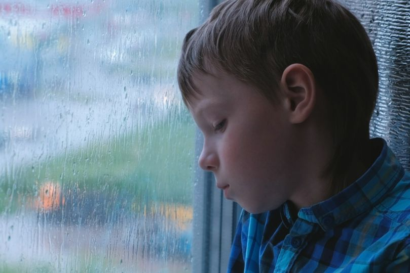 Boy looks out the window in the rain and is sad.