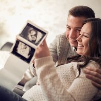 Young pregnant couple looking at ultrasound image