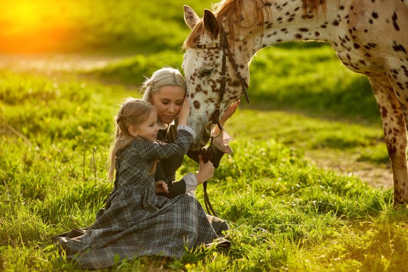 Beautiful woman and girl embracing horse