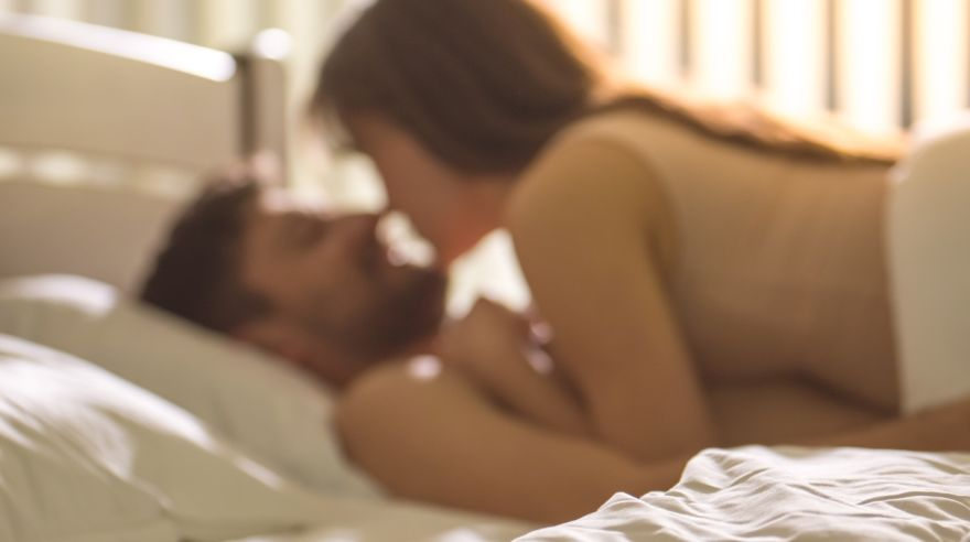 The young couple kissing in the bed