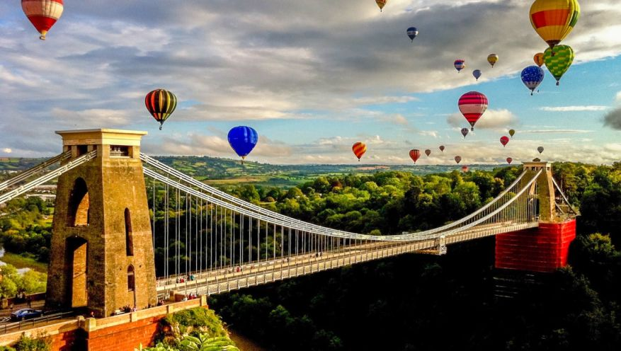Hot air balloons over suspension bridge in the English countryside