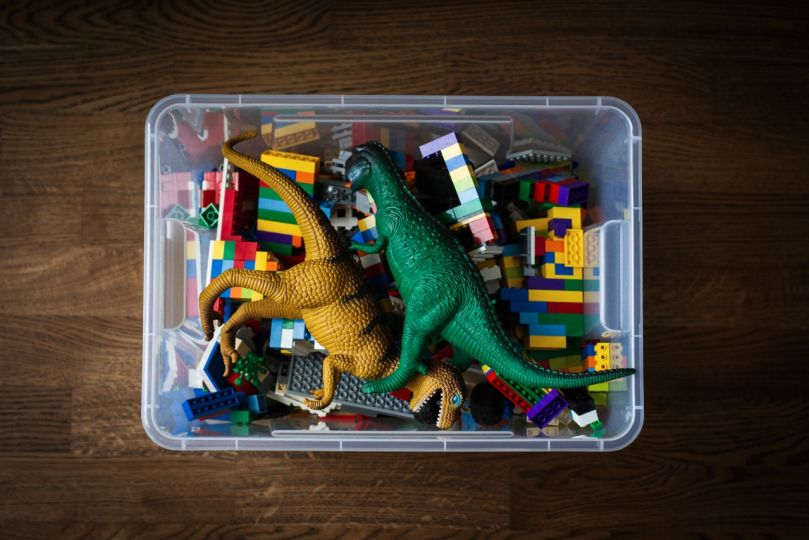 transparent toy container with colored bricks and dinosaurs