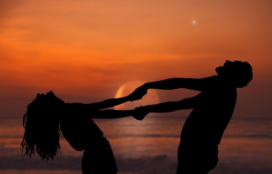 Silhouettes of a couple dancing under the rising Moon and stars over the ocean / sea horizon. My astronomy work.
