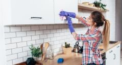 Woman in gloves cleaning cabinet with rag at home kitchen.