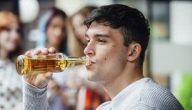 Man Drinking Lager At Social Gathering