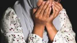 Young Muslim girl sitting in dark room feeling pain with life problem. Crying muslim female holding painful hand, suffering from husband violence