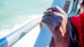 close up of thin and skinny african migrant man hand on boat while crossing mediterranean sea to europe on sunny day as symbol of refugees crisis
