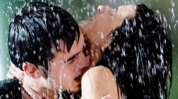 Young couple hugging and kissing under a rain