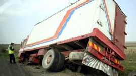 Truck lying in a ditch with policeman investigating