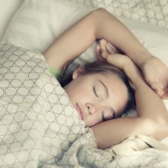 Young girl peacefully sleeping in light bedsheets.