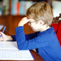 Portrait of frustrated crying sad school kid boy at home making homework. Little child writing with colorful pencils, indoors. Elementary school and education