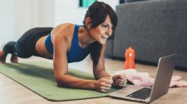 Sporty woman doing plank in front of her laptop