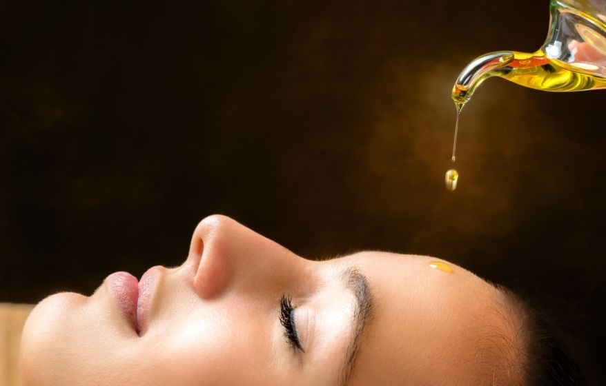 Aromatic oil dripping on female face.