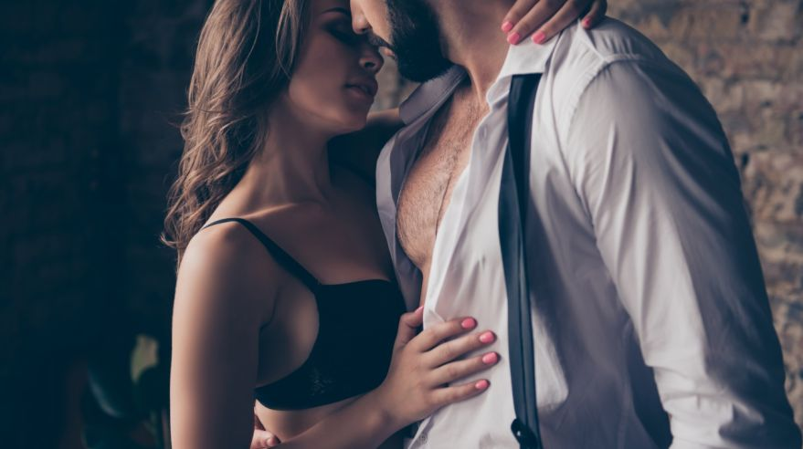 Pure seduction. Cropped close up photo of two naughty lovers, she is gorgeous in black lingerie, he is a business man in classy wear, they are so hot, horny and seductive