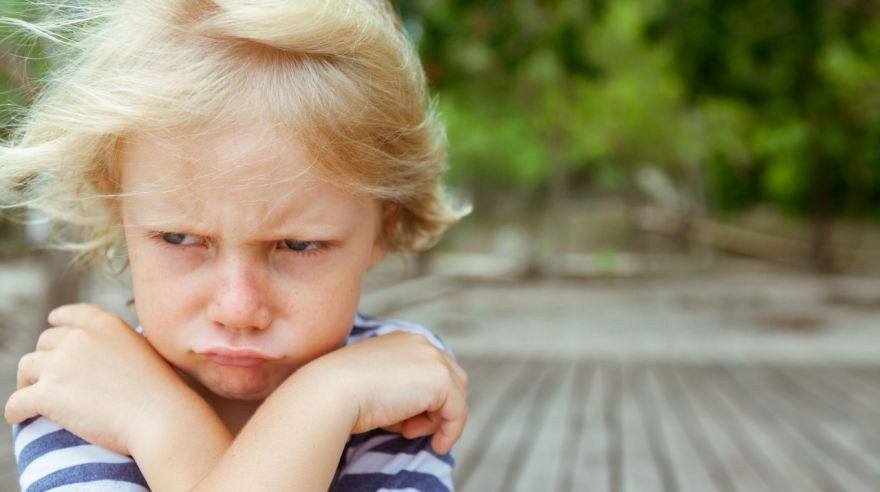 Face portrait of annoyed, unhappy caucasian kid with crossed arms
