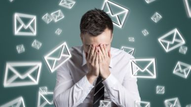 Email symbols swirling around an overstrained man
