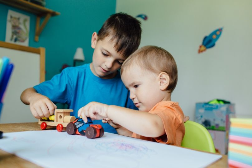 Two brothers playing together with toy cars