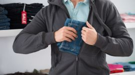 Man Hiding Jeans In Jacket At Store